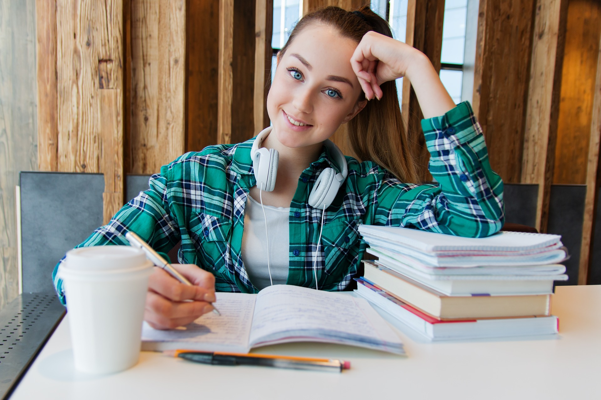 Girl student studying with headphones a notebook and coffee